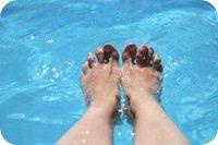 Female feet in pool water